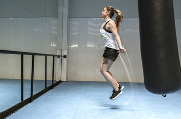Young woman in gym skipping rope