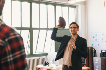Man in office throwing rugby ball smiling