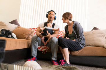 Mother beside father with baby in carrier, playing video game