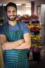 Male florist with arms crossed in flower shop