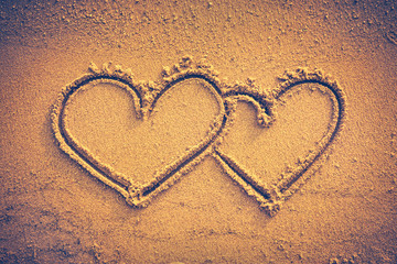Two hearts handwritten on seashore sand. Vignette and vintage tone