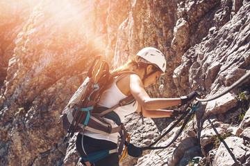 Single fit woman climbing side of mountain