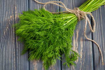 Bunch of fresh organic dill on the rustic wooden table