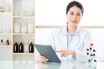 asian female chemist use notepad to research for future Chemical