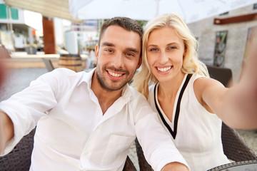 happy couple taking selfie at restaurant terrace
