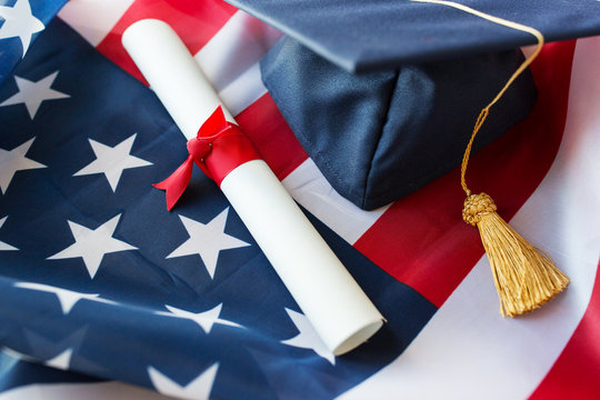 mortarboard and diploma on american flag