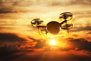 Drone flying at sunset. Sun shining on dramatic sky.
