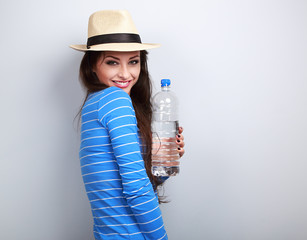 Healthy casual woman in summer hat holding bottle of pure water