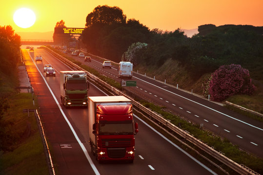 trucks in the highway at sunset