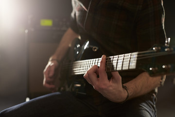 Close Up Of Man Playing Electric Guitar In Studio