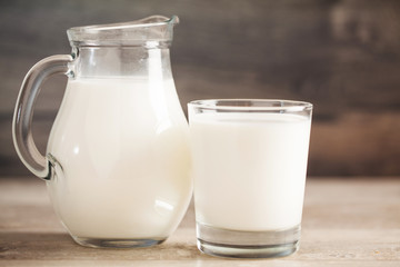 fresh milk in glass jug and glass on wooden background. Selective focus.
