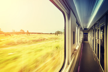 Retro stylized window frame in train at sunset, travel concept with motion blurred view outside.