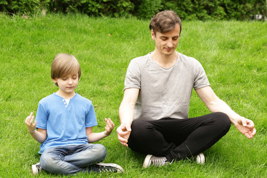 father and son sitting on green grass and meditates