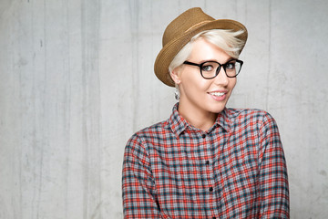 Young fashion smiling girl hipster with short blond hair hat and shirt