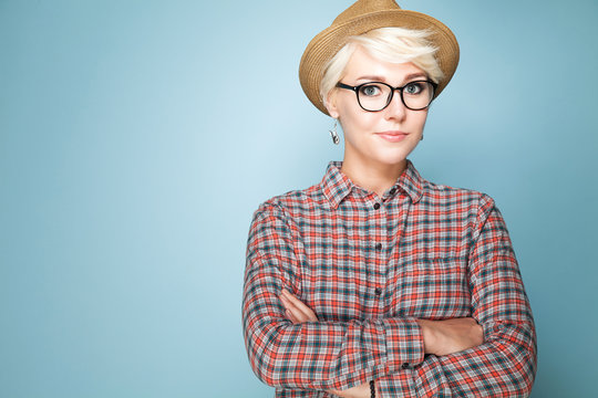 Young fashion woman with short blond hair in hat and shirt with glasses