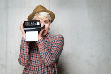 Young fashionable hipster smiling girl with a camera for snapshots