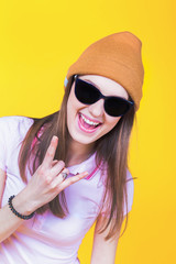 Young teenager wearing a hat and sunglasses pointing to empty
