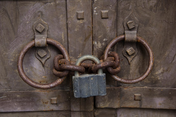 Steel padlock keeping the old door