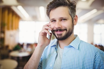 Portrait of smiling businessman using phone in cafeteria