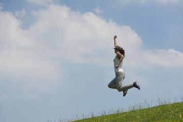 青空に向かってジャンプする女性