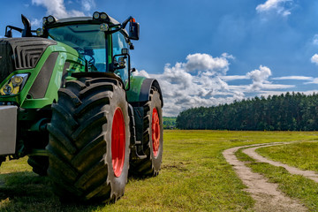 Part of the tractor standing in a field near the road. Wall mural