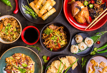 Assorted Chinese food set. Chinese noodles, fried rice, dumplings, peking duck, dim sum, spring rolls. Famous Chinese cuisine dishes on table. Top view. Chinese restaurant concept. Asian style banquet Fototapete