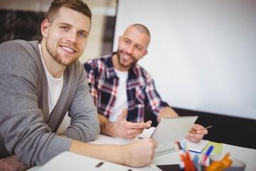 Young businessmen using digital tablet at desk in office