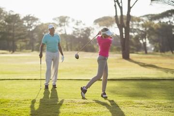 Mature golfer playing by man