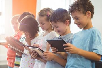 Smiling children using digital tablets