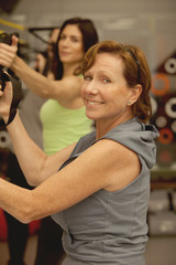 Senior woman exercising with suspension bands at fitness center class