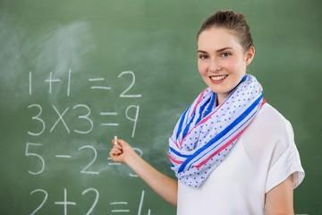 Portrait of teacher teaching mathematics in classroom