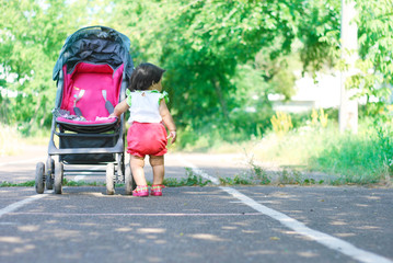 Baby girl standing near a baby carriage