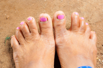 feet of old Asian woman standing on cement floor.