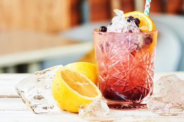 Alcoholic cocktail consisting of currants, blackberries, and liqueur in a glass and lemon on a wooden table