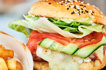 A hamburger consisting of meat patties, cheese and vegetables close up