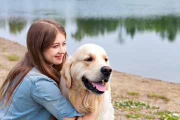 Young woman with the golden retriever in the park
