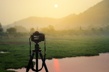 Dslr photo camera on tripod is travel photographer equipment shooting atmosphere during sunrise,sunset (with clipping path).Traveling and Relax Concept