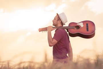 Young retro styled man with acoustic guitar over his shoulder walking through the wheat field. Sun and clouds in the background. Music, art and lifestyle concepts.