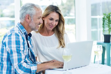 Couple looking in laptop on table