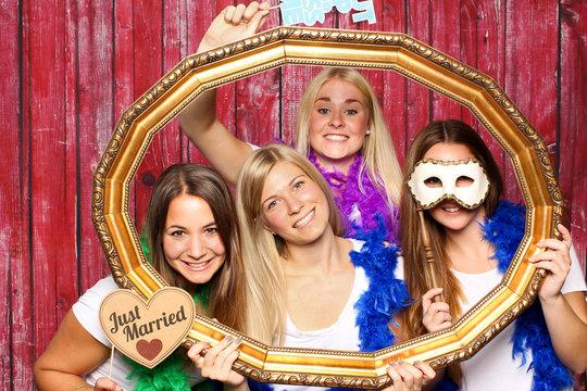 Hochzeitsgesellschaft vor einer Fotobox - Junge Mädchen mit Probs schauen durch einen Rahmen