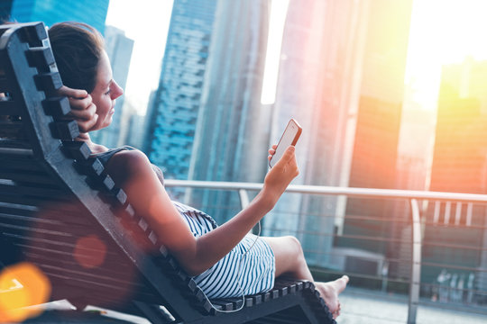 Woman with mobile phone resting on deck chair near skyscrapers (intentional sun glare and lens flare effect)