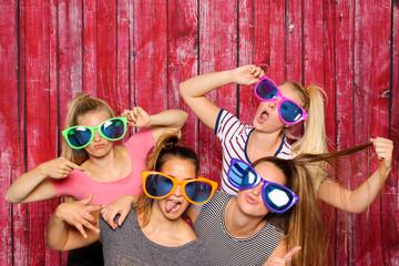 Mädchengruppe mit Brillen albern vor einer Fotobox - freche Mädchen mit Sonnenbrillen