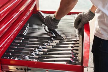 Hand picks a tool for car repair