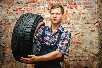 Handsome young man holding a tire in a car repair or maintenance shop, against red brick background (natural light)
