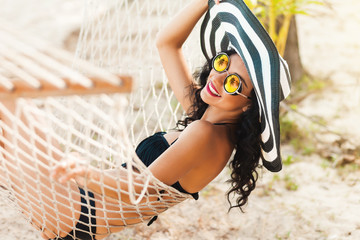 Pretty amazing cheerful young girl on the beach, lying in a hammock and smiling in a black sexy bikini in a wide luxurious hat and mirrored sunglasses are reflected palm trees, lifestyle, tanned