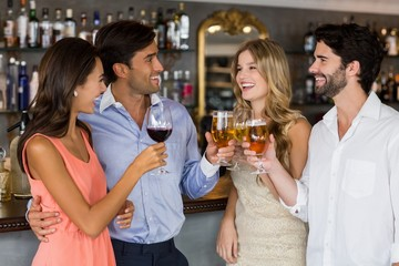 Group of friends toasting red wine and champagne