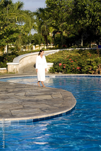 Femme en peignoir qui se balade au bord d 39 une piscine for Peignoir piscine