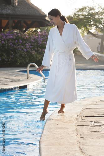 Femme souriante en peignoir au bord d 39 une piscine for Peignoir piscine