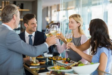 Business colleagues toasting beer glasses while having lunch