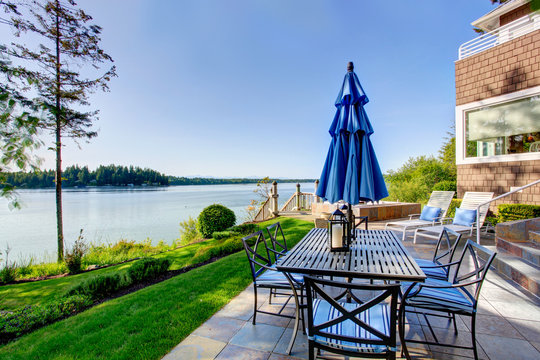 Luxury house exterior with impressive water view and cozy patio area.